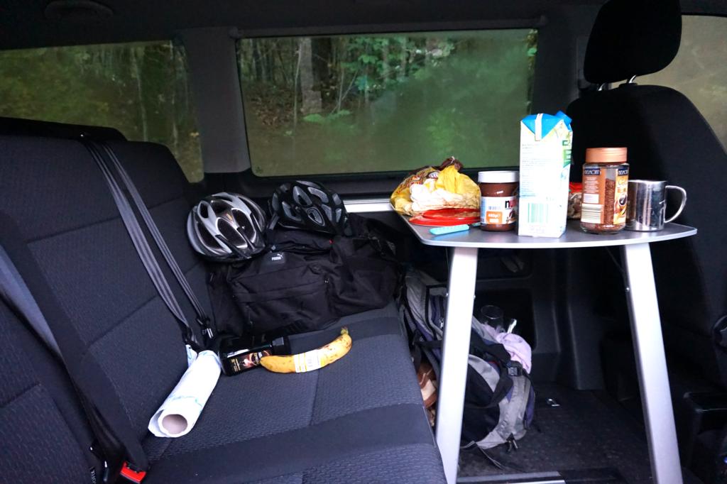 Frühstück im T6 Multivan mit Drehsitz und Campingtisch im Innenraum.